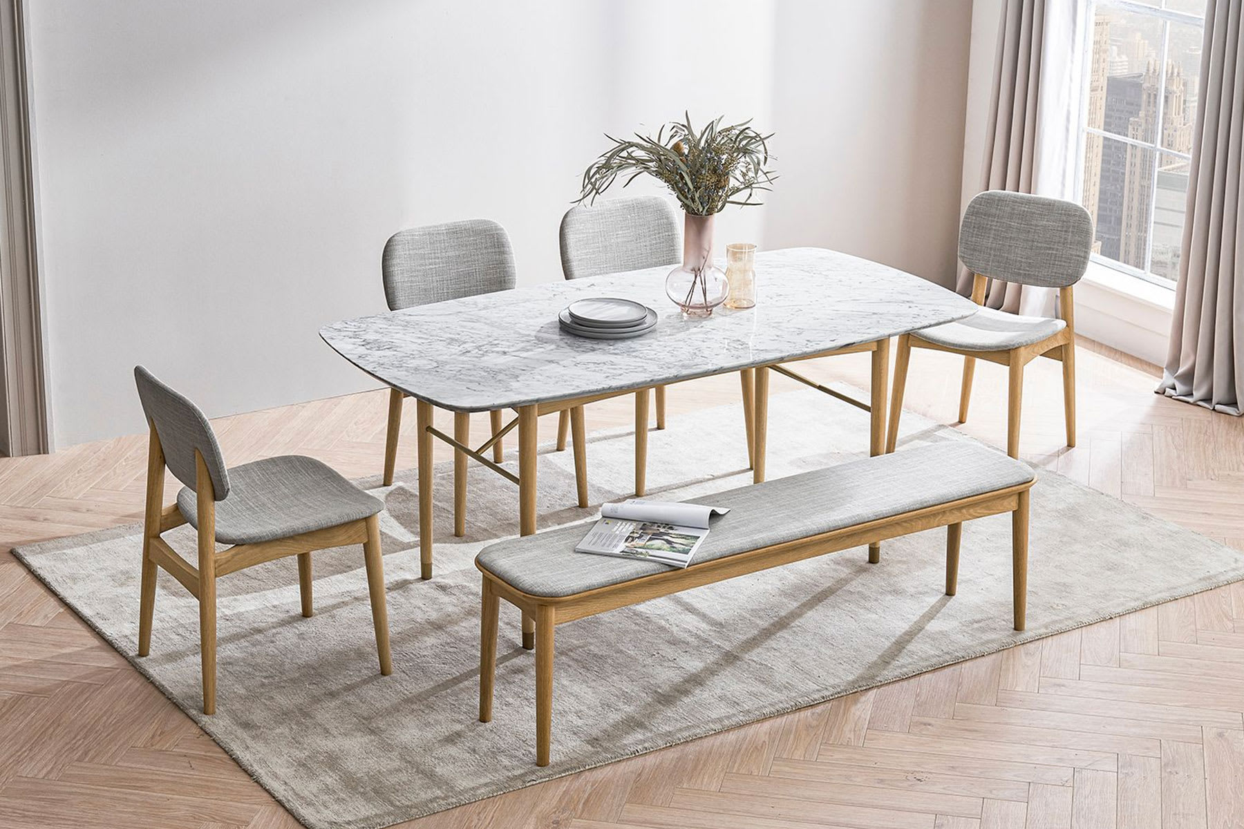 Rounded marble tapletop dining table, chairs and plant in dining room
