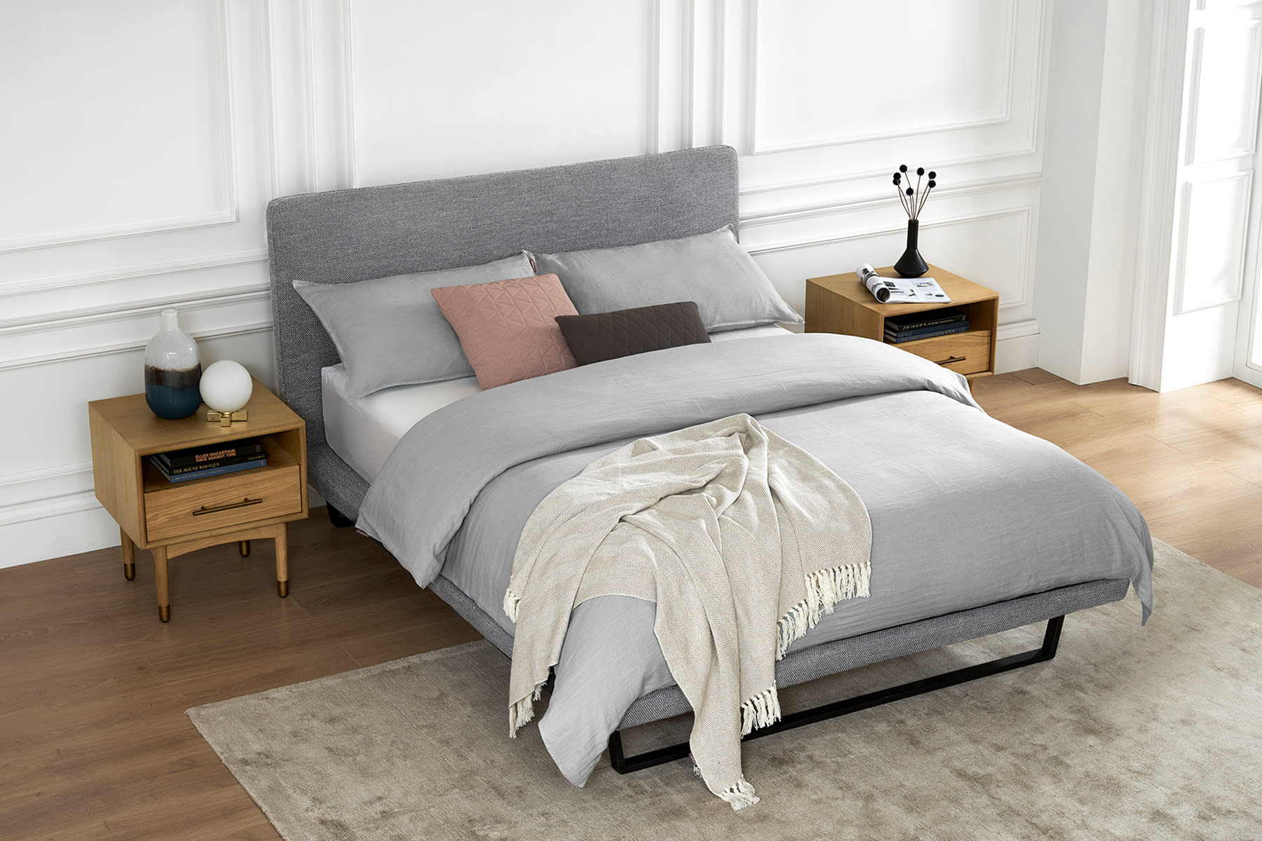light gray upholstered fabric bed with sofa, bedside table and plant in bright room