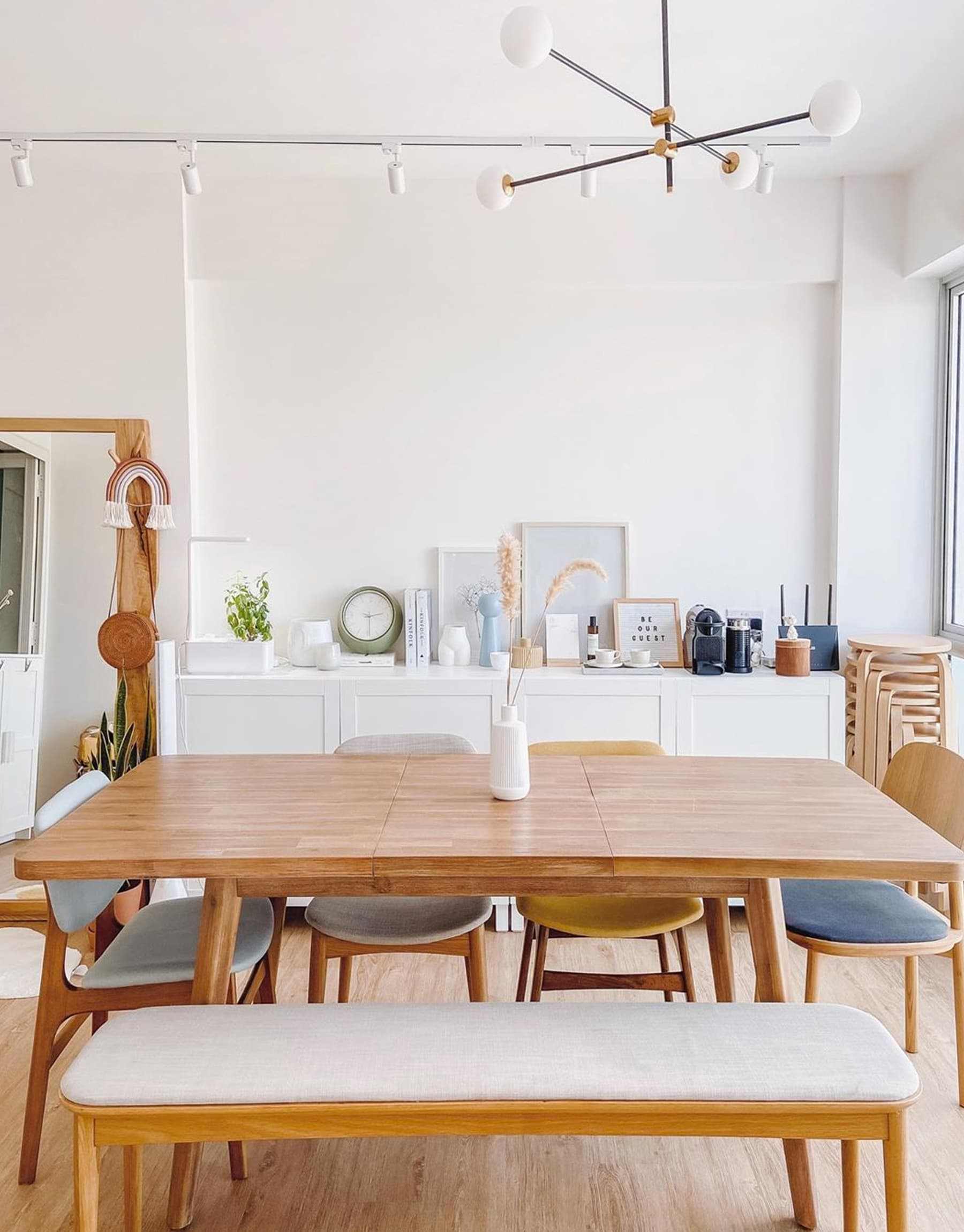 mismatched dining table and chairs in scandinavian dining space with sideboard
