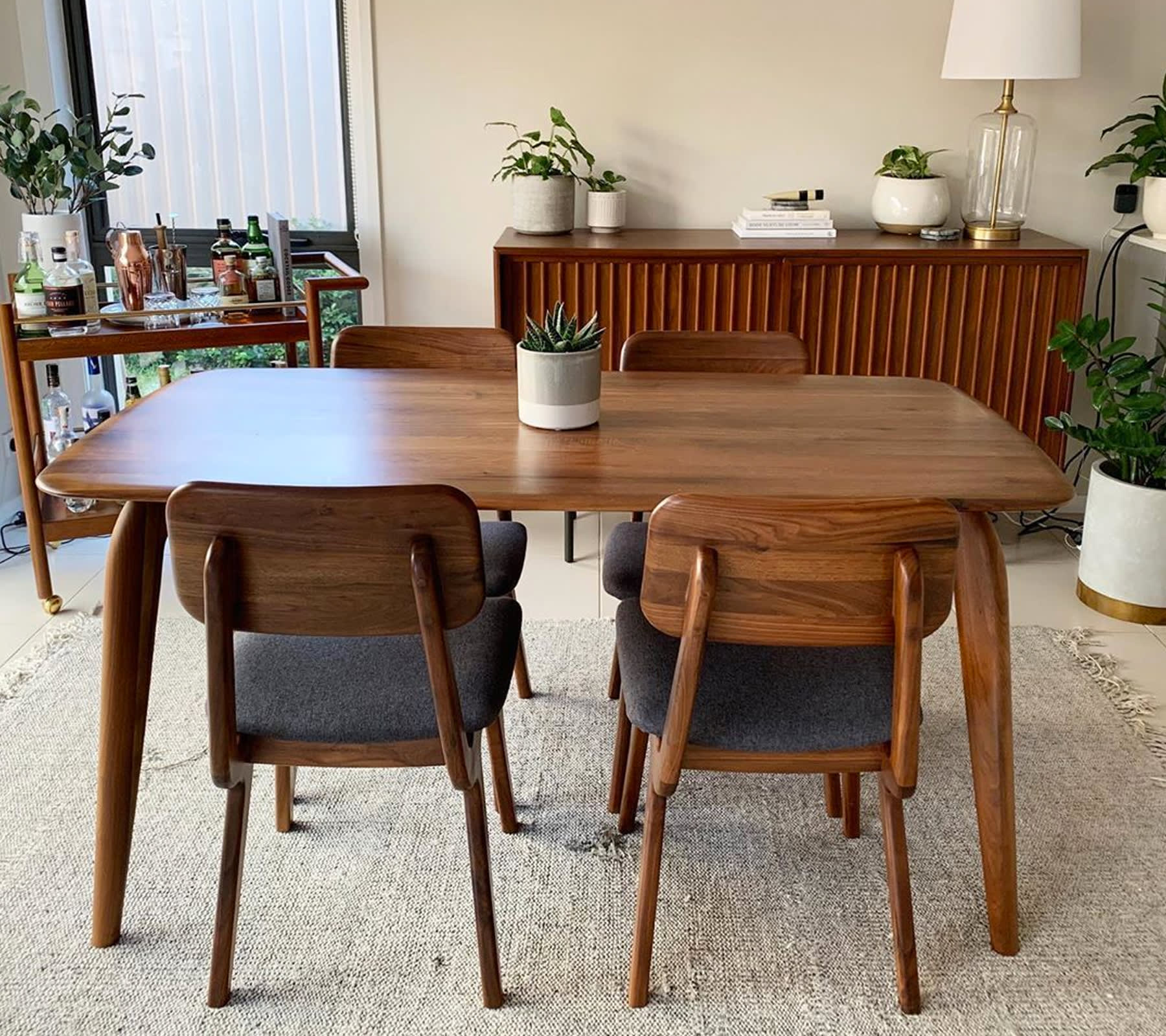 dark wooden dining table and chairs in mid-century modern dining space with bar cart and sideboard