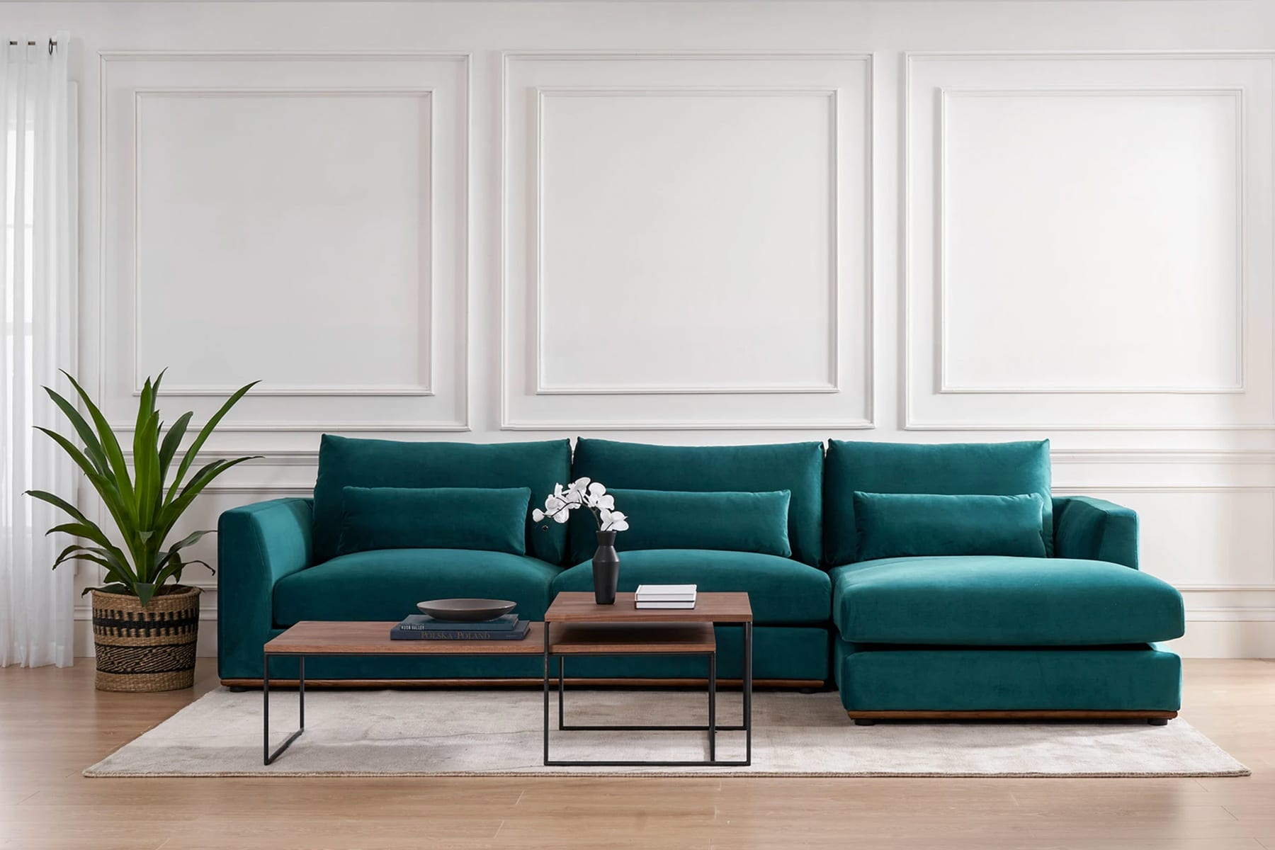teal velvet sofa, coffee table and potted plant in a bright living room