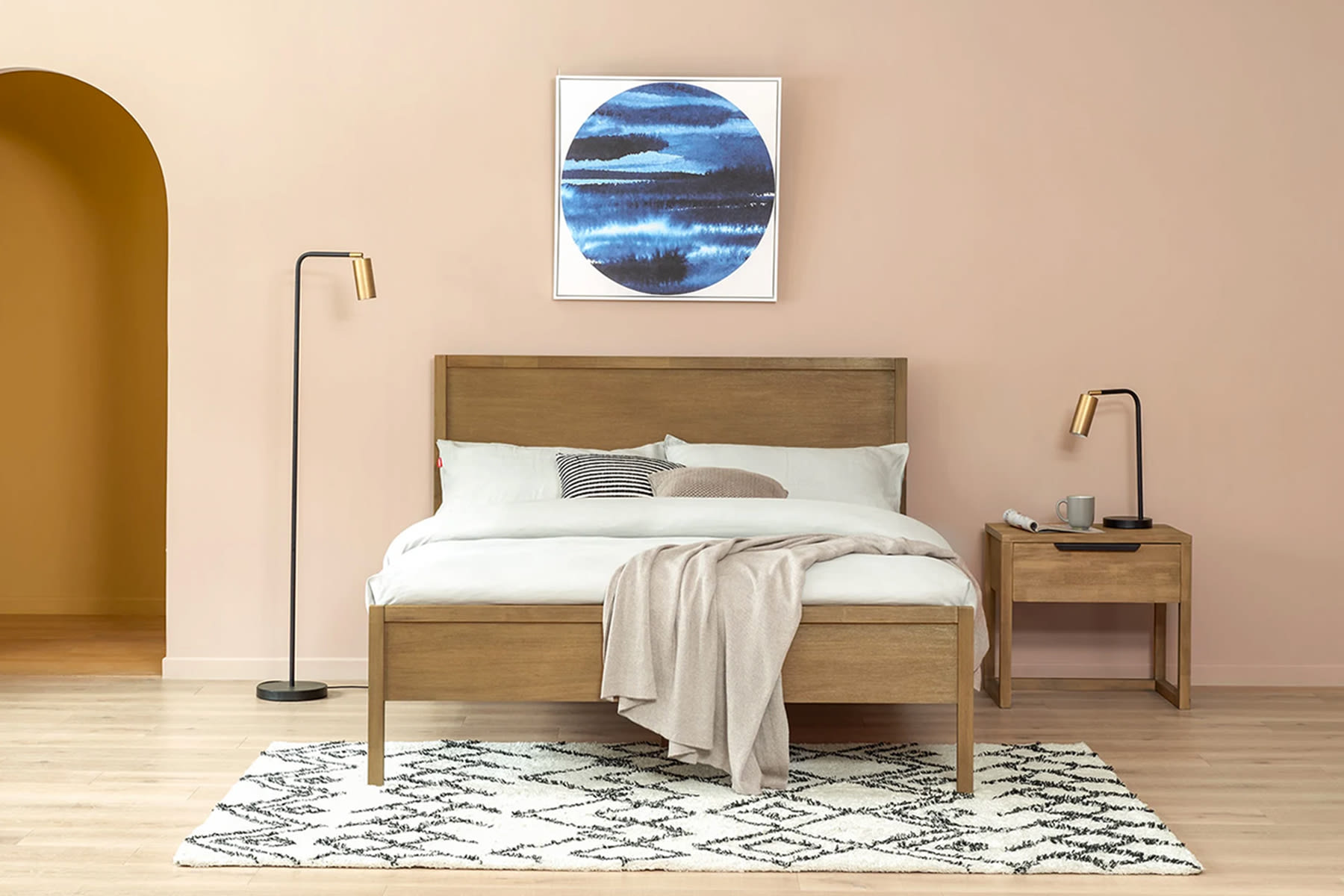 wooden bed frame, hanging wall art and bedside tables in pastel bedroom