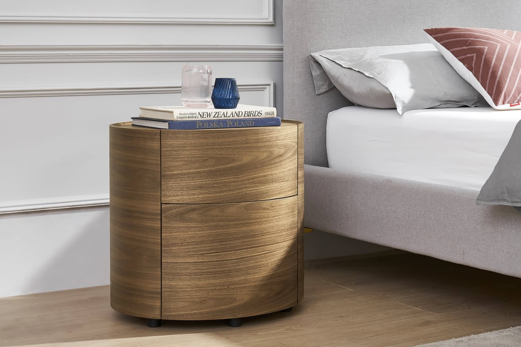 round wooden bedside table with books and mugs beside bed