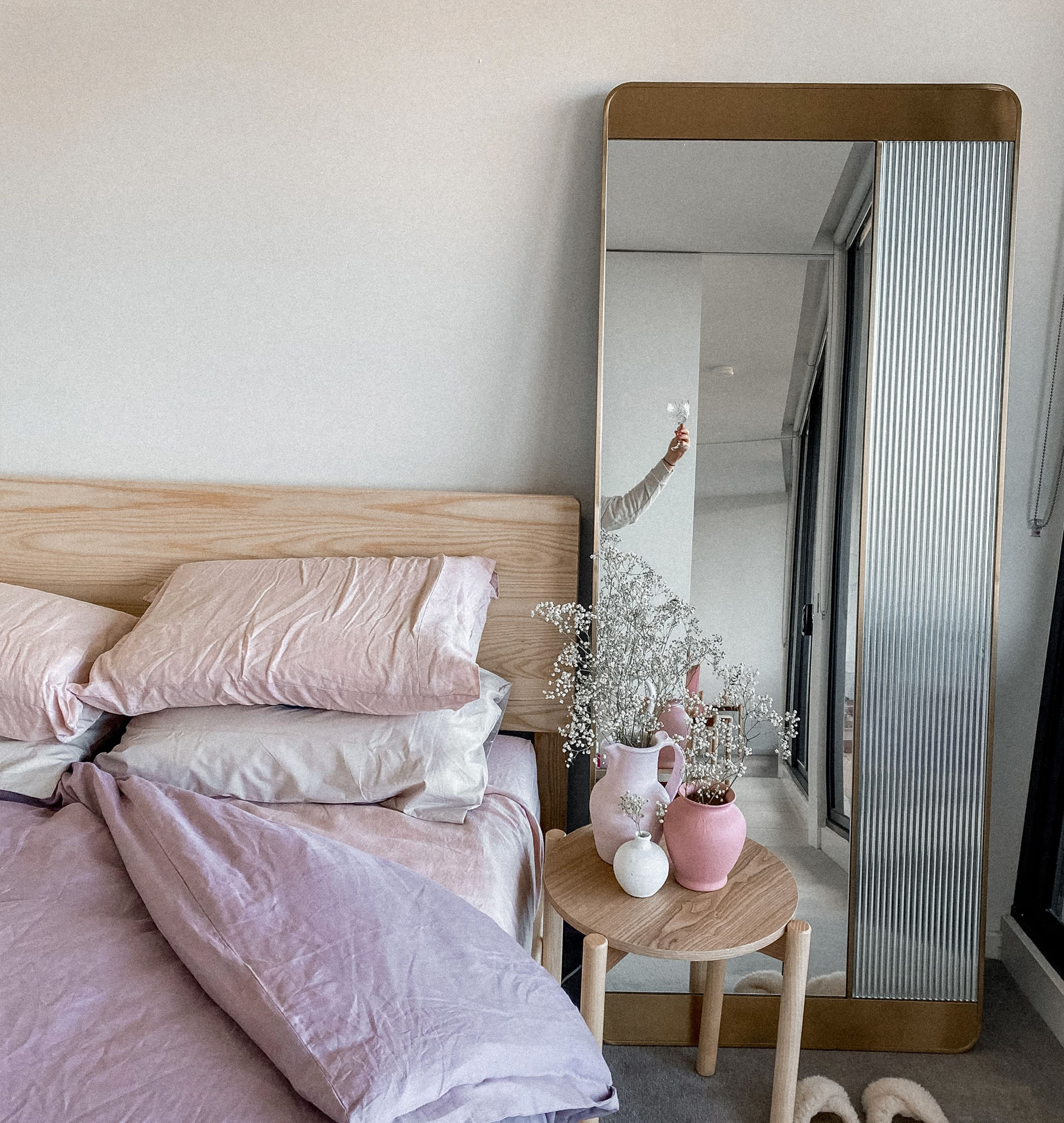 standing mirror with ribbed glass detail in bedroom next to bed and bedside table
