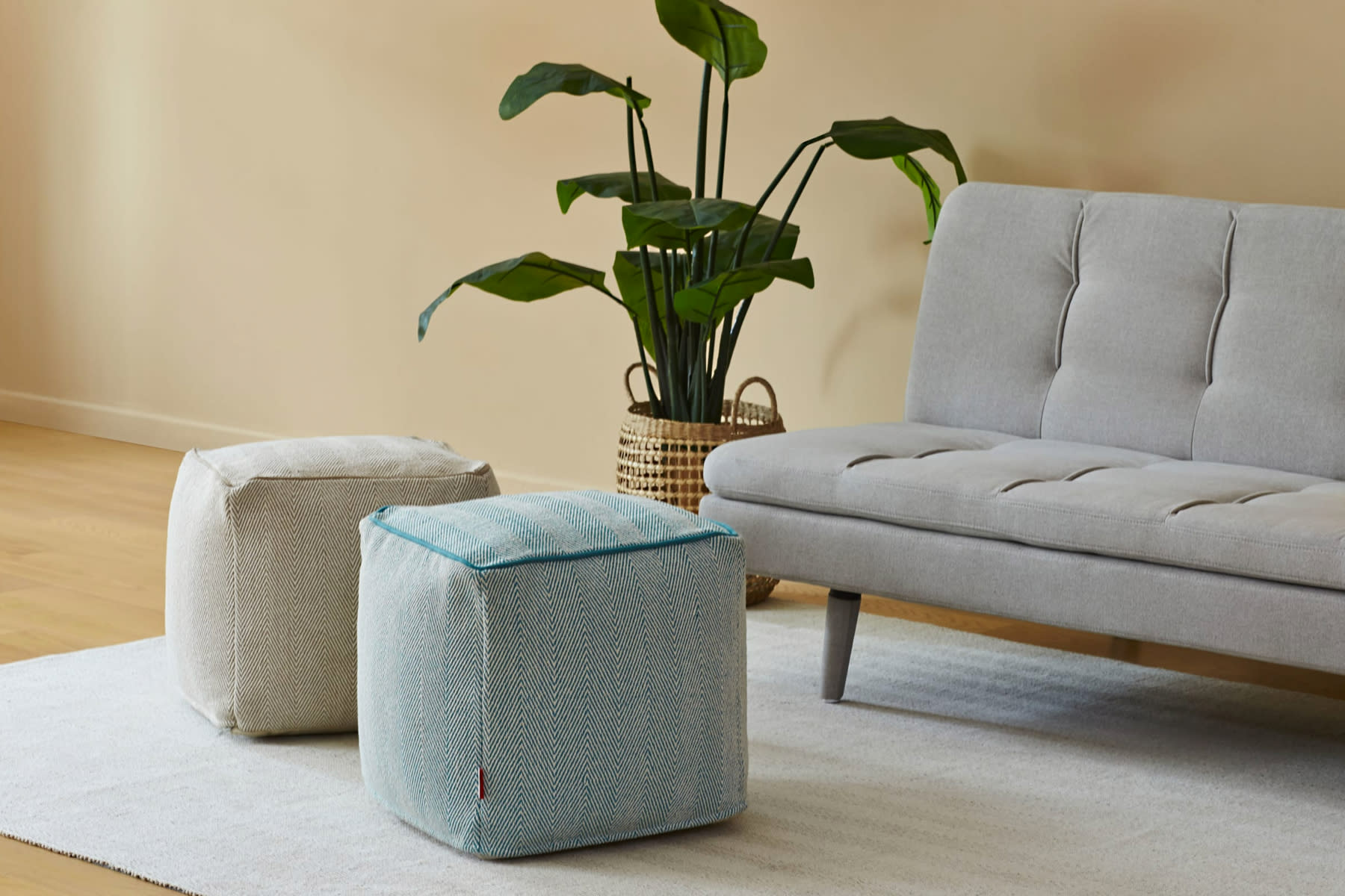 fabric poufs in living room next to fabric sofa and potted plant