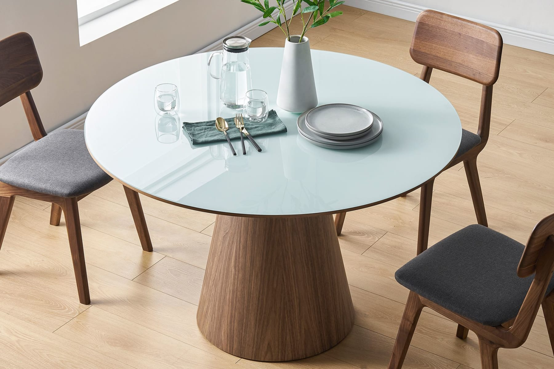 Round dining table glass tabletop, chairs and pastel painting on sideboard