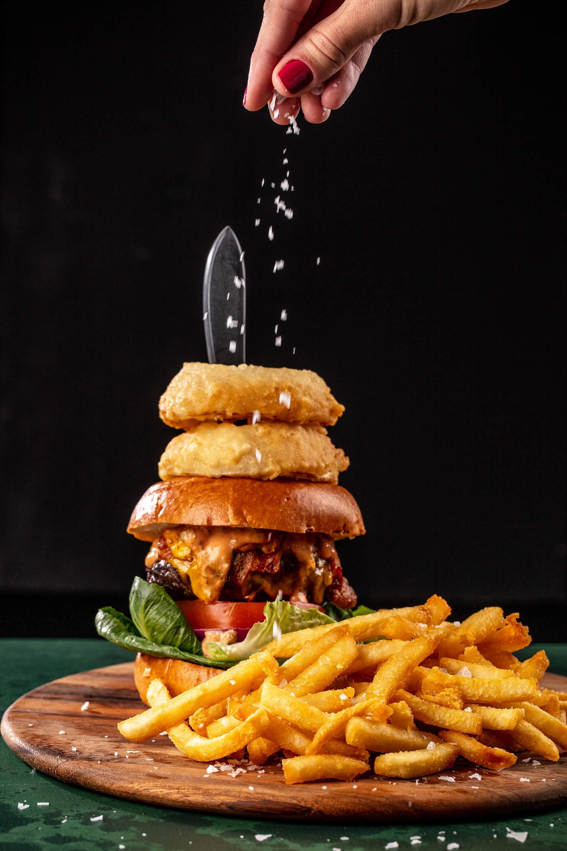 Cavo Restaurant Sprinkling salt on burger