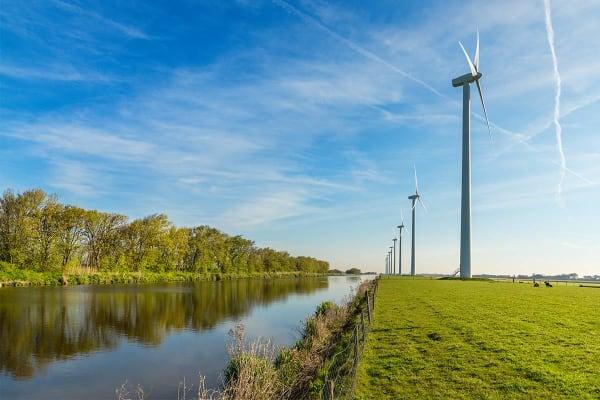 Afbeelding met windmolens in een weiland dat de een onderzoek naar duurzame energie en de duurzaamheid van energieleveranciers uitbeeldt.