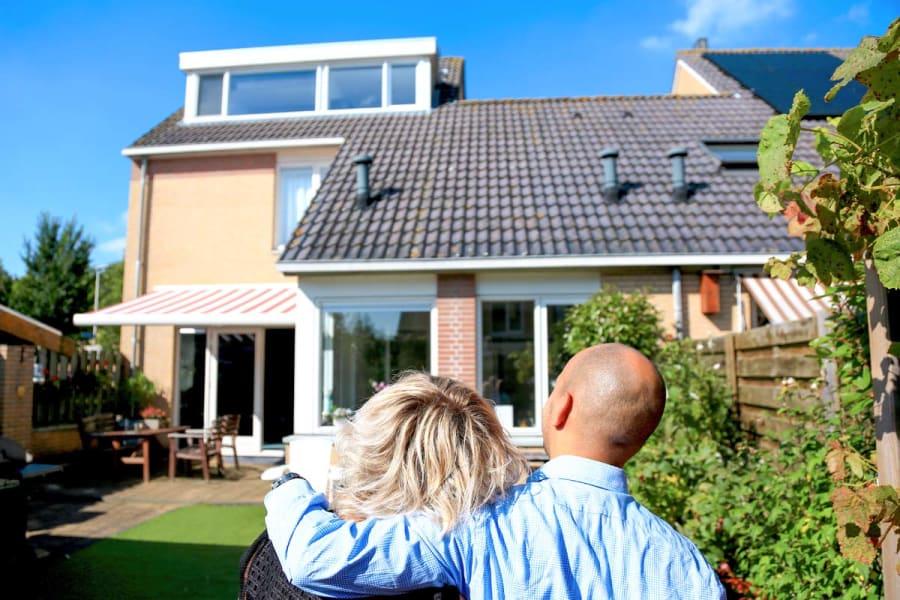 Afbeelding van twee mensen die gearmd naar een huis kijken op een zonnige dag. De afbeelding ondersteunt een kader dat linkt naar een topic over subsidies en leningen voor energiebesparende maatregelen op de homepage van het dossier energie vergelijken.