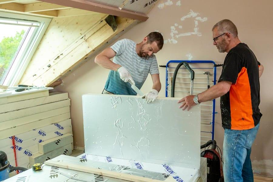 Afbeelding van twee mannen die een isolatieplaat op maat snijden. De afbeelding ondersteunt een kader dat linkt naar een topic over isoleren van woningen op de homepage van het dossier energie vergelijken.