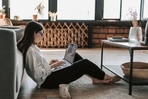Jobseeker working at home, sitting on the floor with a laptop and a cup of coffee