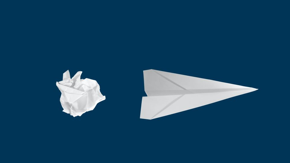 Crumpled up ball of paper behind a paper airplane