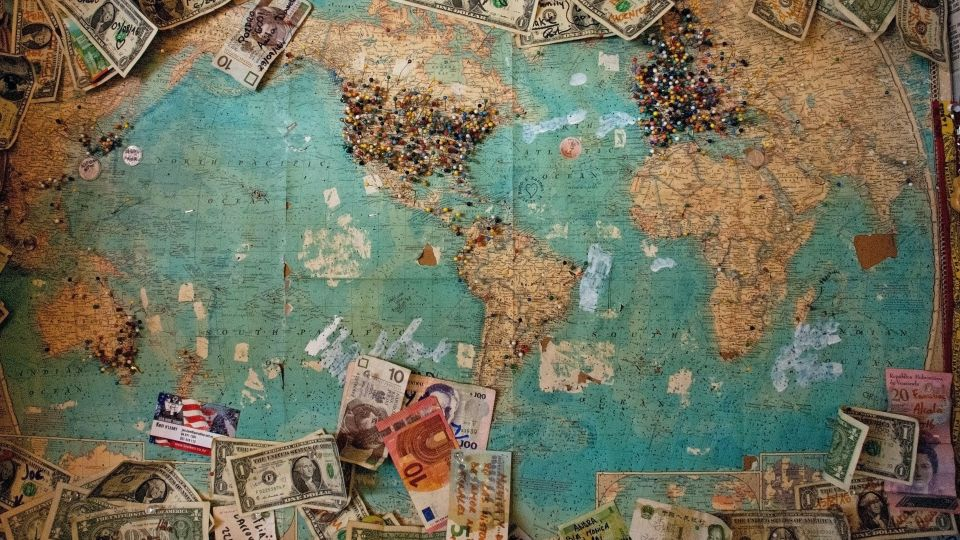 World map surrounded by paper money, with pins stuck into various countries