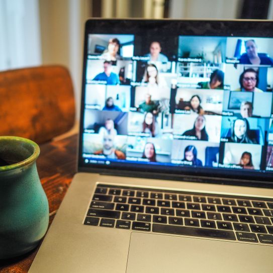 an open laptop computer shows a remote meeting in progress