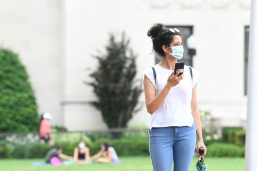 A woman in a facemask walks through campus
