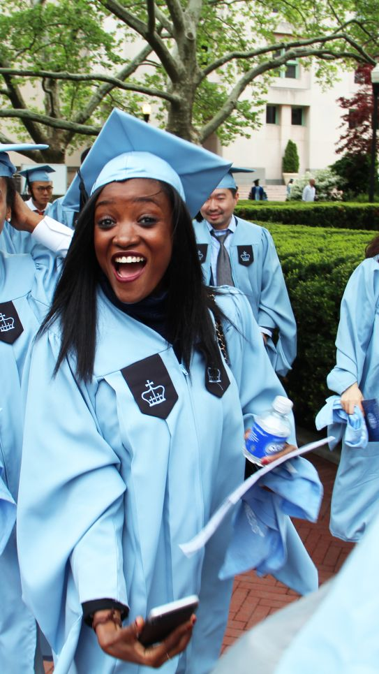 A student smiles excitedly at the camera while proceeding to the graduation ceremony