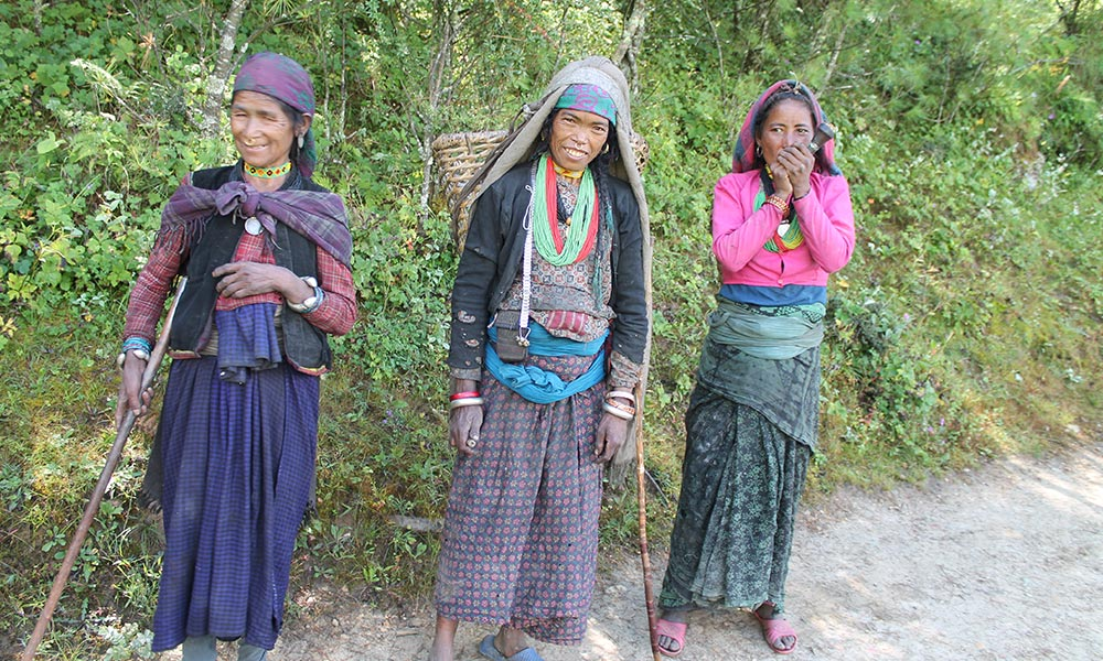 Indigenous women, dressed with their traditional ornaments and smoking pot