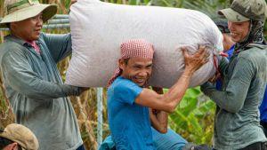 A Vietnamese man carries a rice bag