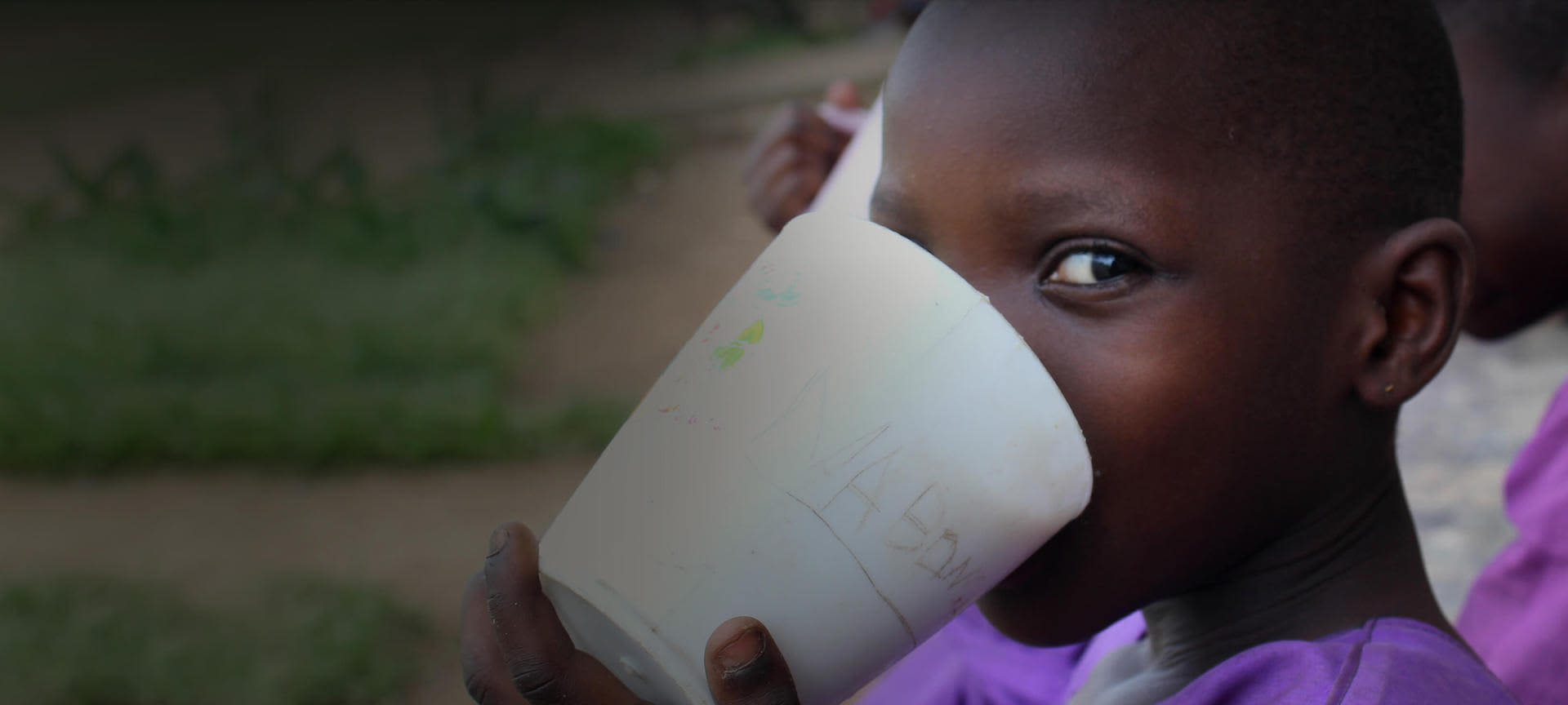 In this article you'll learn how to sponsor a child. This image shows an african school girl eating her lunch