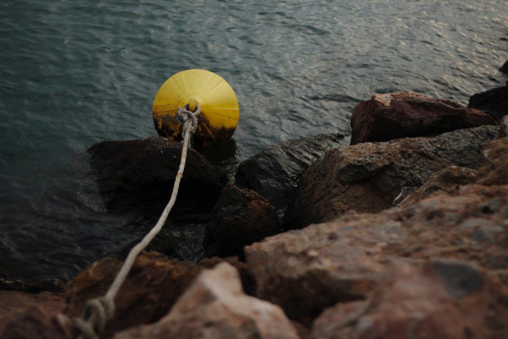 A bouy floating on a rocky shore
