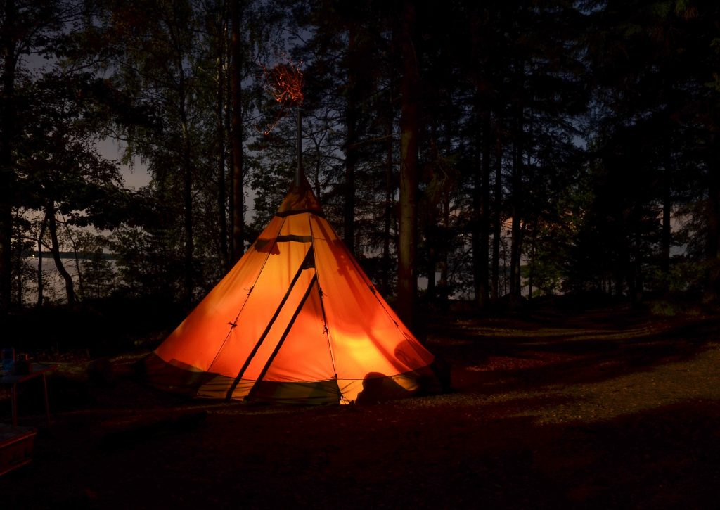 An illuminated tent alone in the woods at night