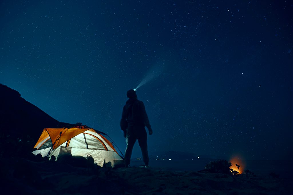 A camper looking into the night sky with a headlamp pointed upwards.