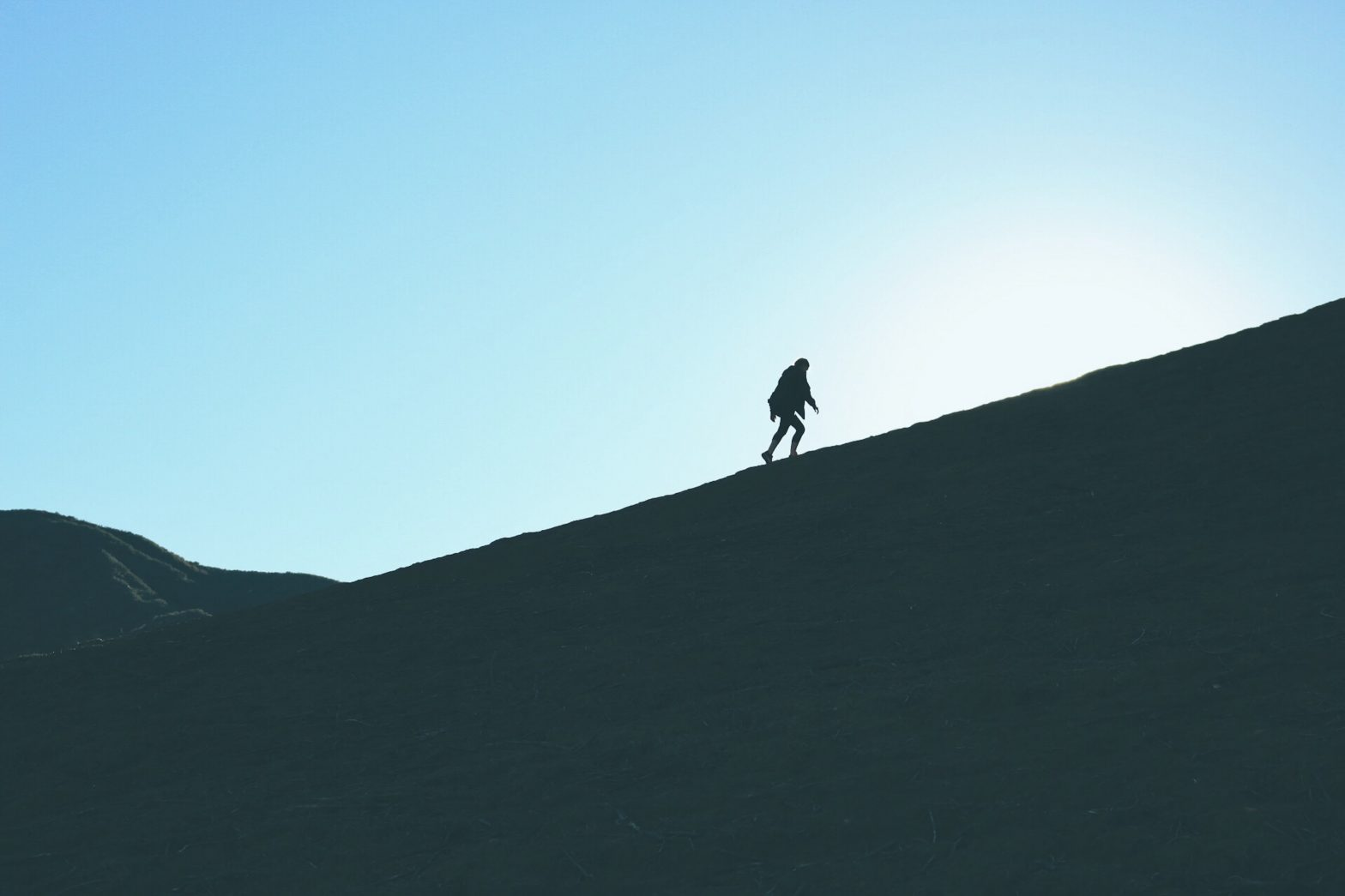 Silhouette of a man climbing a mountain