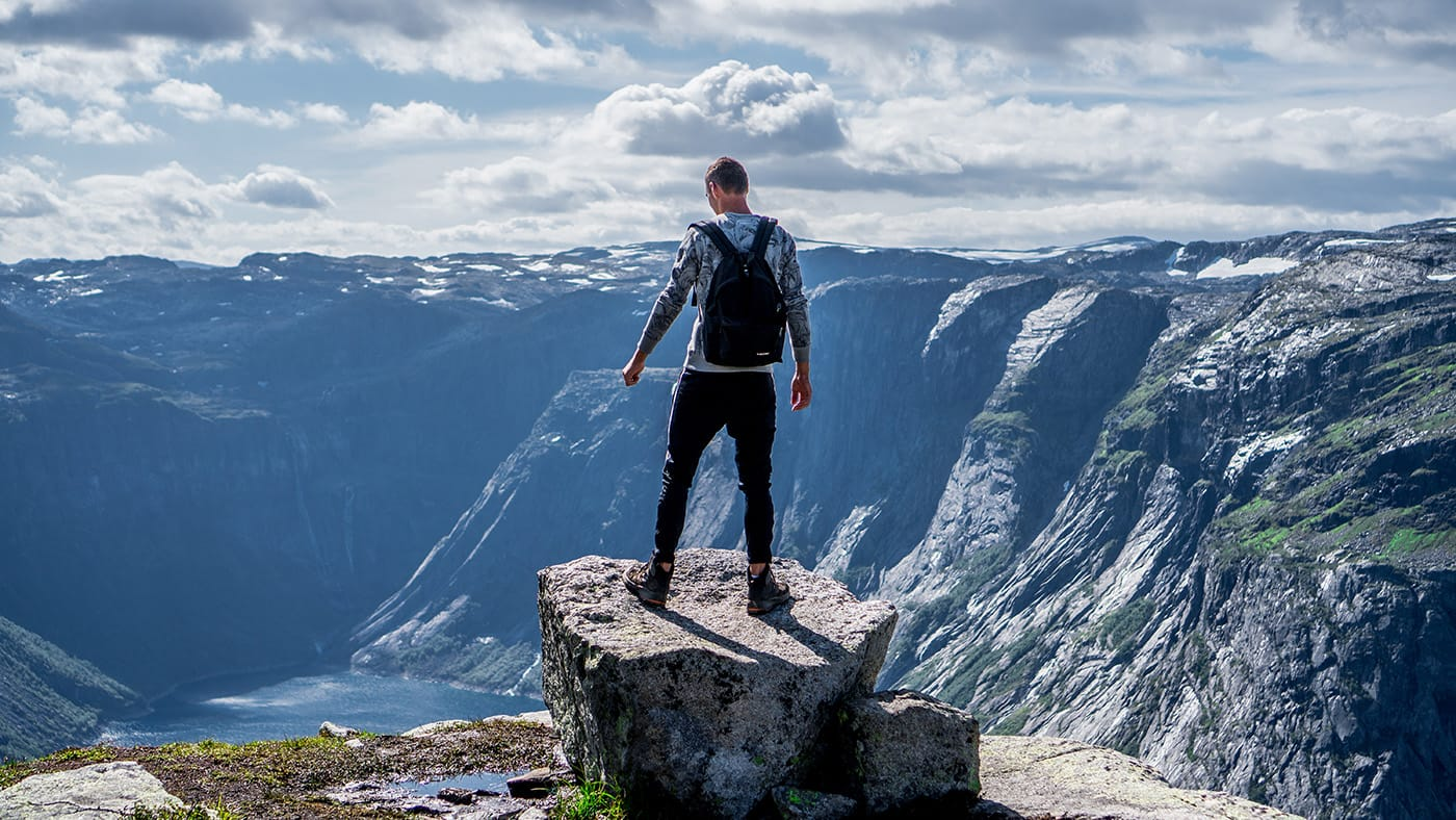 A man standing on a rock at the top of a mountain, overlooking a valley
