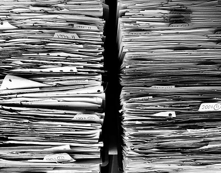two tall stacks of files and documents