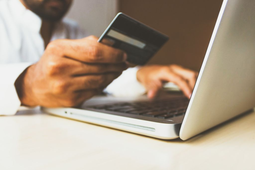man using his credit card and laptop for online bill payment