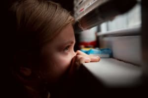 Ein Kind späht zwischen den Storen durch.