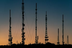 Cellular towers stand tall in the sunset