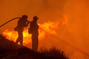 Two forest fire fighters engage fire with hose