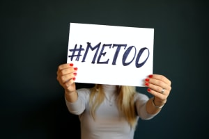A women holds up a sign with the hashtag '#metoo' written on it