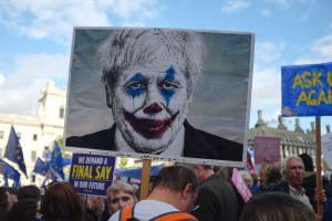 A portrait of UK Prime Minister on a sign, altered to look like that of the character Joker from the 2019 major motion picture Joker.