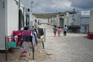 Several small children walk together amongst the temporary shelters in the Moria Refugee Camp