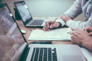 Das Bild zeigt zwei Personen, die am Laptop arbeiten.