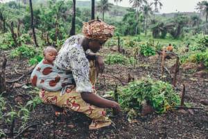Das Bild zeigt eine Afrikanische Frau im Garten
