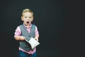 Das Bild zeigt einen kleinen Junge mit einem Buch