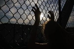Eine Person steht hinter einem Gitter und sehnt sich nach Freiheit.