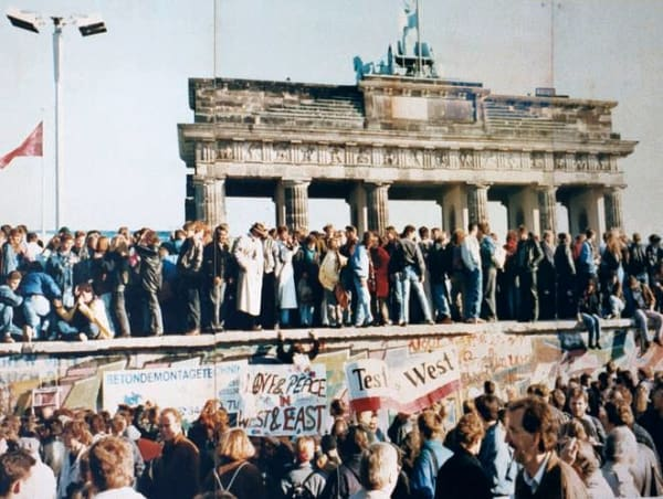 The Fall of the Berlin Wall, 1989. The photo shows a part of a public photo documentation wall at the Brandenburg Gate, Berlin - Via Wikimedia Commons