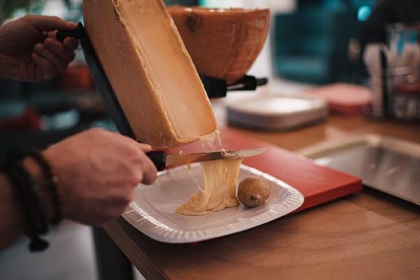 Raclette ist ebenfalls eine Spezialität der Schweiz, die aus geschmolzenem Käse besteht.