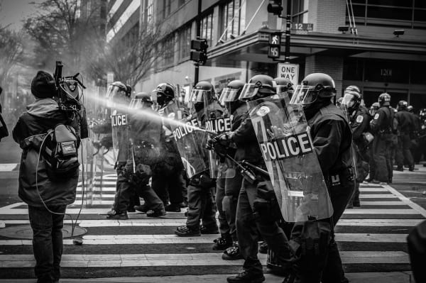 A cameraman stands feet from riot police using pepper spray