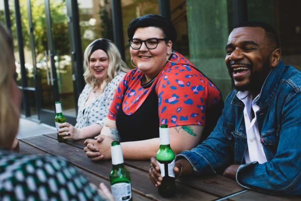 A group of people sitting at a picnic table drinking beer