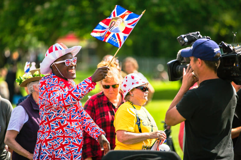 Wedding spectator waving Harry and Meghan Union Jack flag.