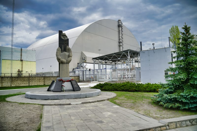 Monument to the victims of Chernobyl in front of the sarcophagus encapsulating reactor 4