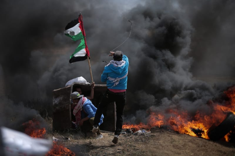 A Palestinian youth throws a stone with a home-made sling through thick black smoke