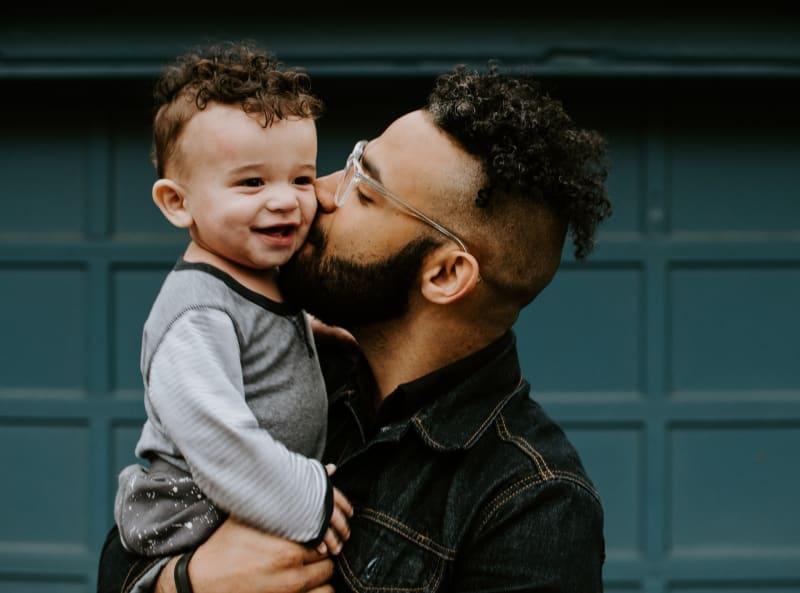 Ein Vater gibt seinem kleinen Kind einen Kuss.