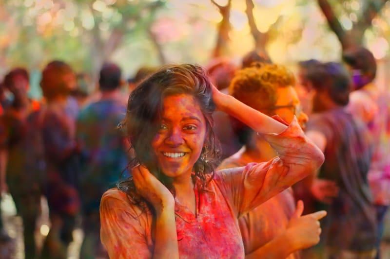 Das Bild zeigt eine Frau in farbengepulverten Kleidern