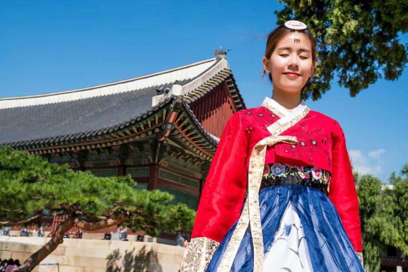 Ein Koreanisches Mädchen steht vor einem koreanischen Palats